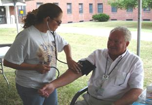 Woman checking a man's blood pressure